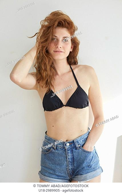 Three quarter length portrait of young redhead woman wearing black bikini and shorts, looking at camera