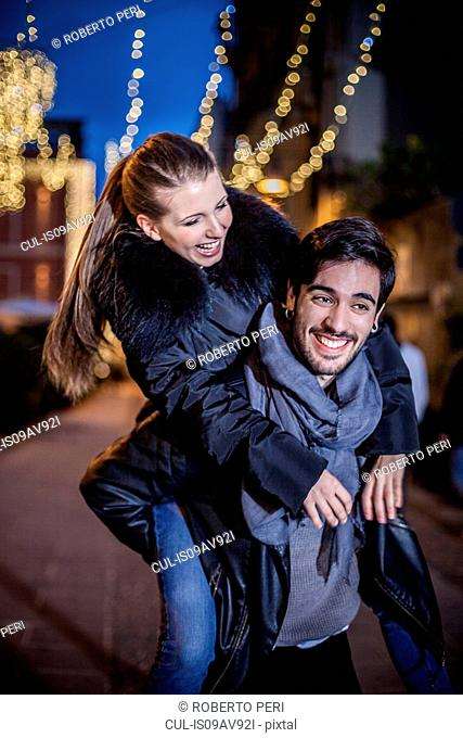 Young man giving young woman piggyback smiling