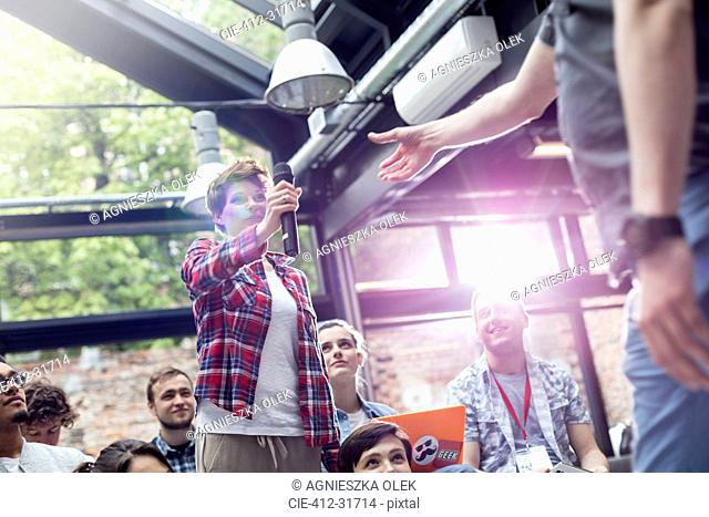 Woman in audience handing speaker microphone at conference