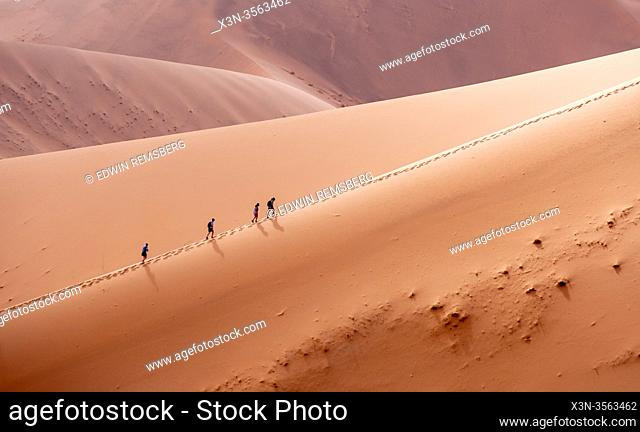 Hikers Hiking Up a Sand Dune in Sossusvlei , Namib-Naukluft National Park , Namibia