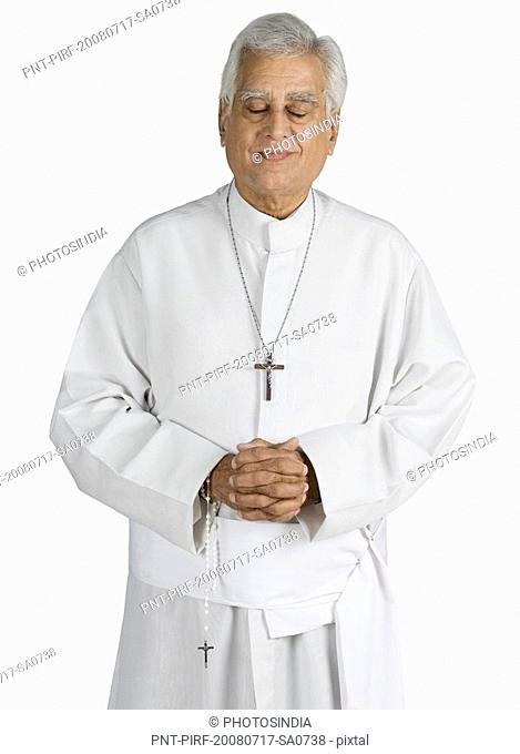 Close-up of a priest standing with hands clasped and smiling