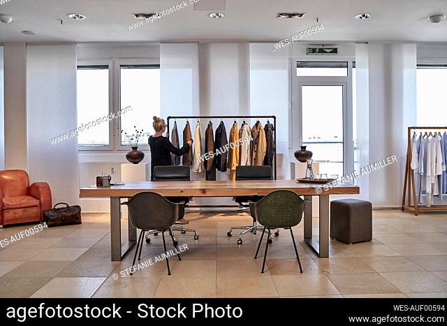 Mature woman shopping at clothes design studio