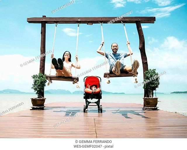 Thailand, Koh Lanta, happy parents on wooden swings in front of the sea and sleeping baby in a stroller
