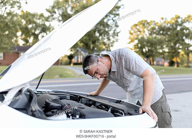 Man checking his car standing at the road side