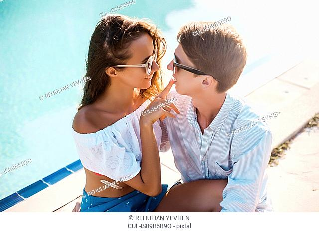 Young woman with finger on boyfriend's lips at poolside, Koh Samui, Thailand