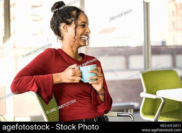 Happy young businesswoman having a coffee break in office