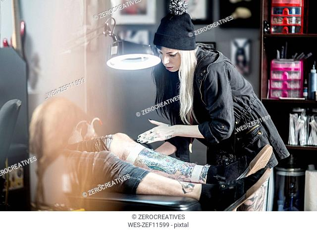 Female tattoo artist applying protective wrap on finished tattoo