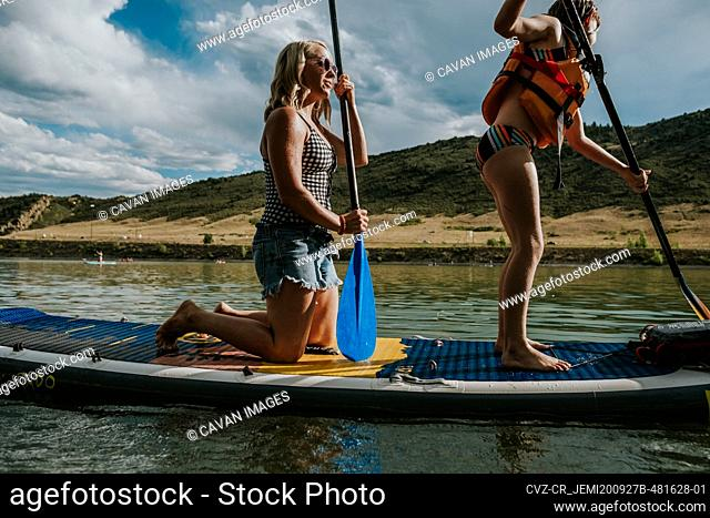 Mom and daughter paddle boarding together on a lake
