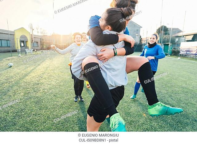 Football players jubilant and hugging on pitch