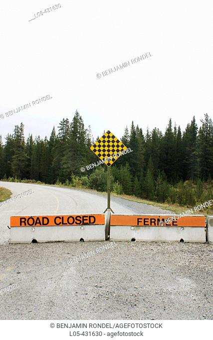 An English and French sign of a closed country road in Alberta, Canada