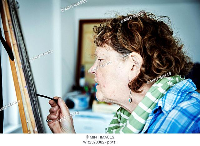 An artist working at her easel, using charcoal on paper to create an artwork