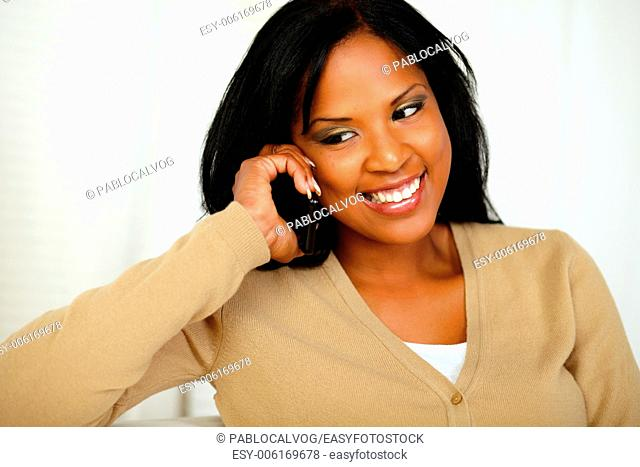 Portrait of a stylish young woman looking down while is on mobile phone at home
