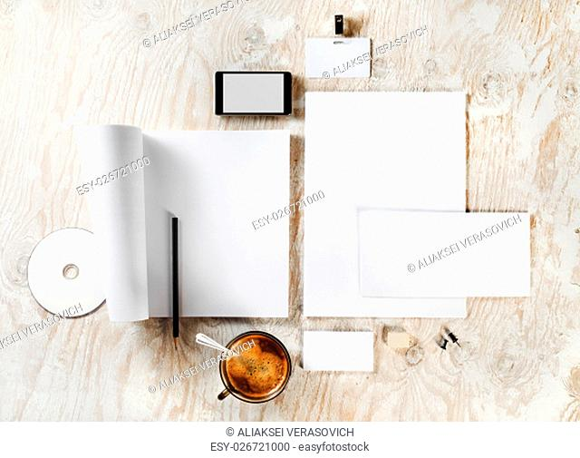 Photo of blank stationery set. Corporate identity template on light wooden background. For design presentations and portfolios