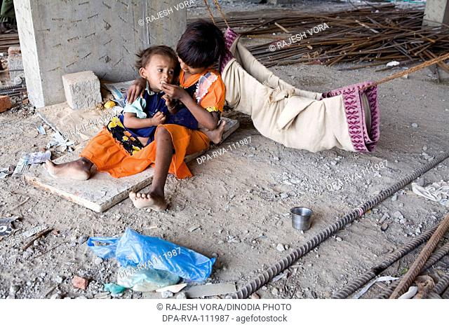 A young girl feeds her sibling at a construction site while their parents are away on work ; Ahmedabad ; Gujarat ;  India