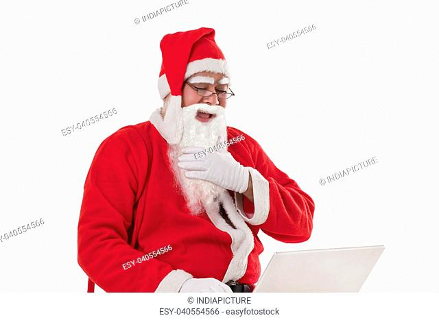 Cheerful Santa Claus using laptop over white background