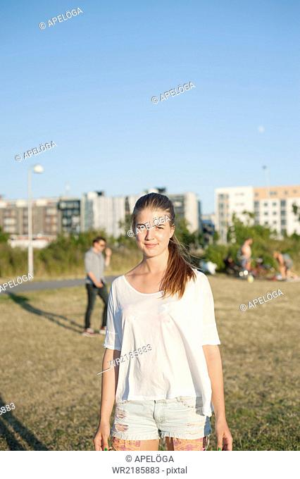 Portrait of young woman standing at park in city