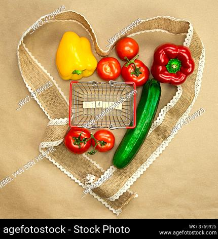 Fresh organic vegetables with the word Health in shopping basket surrounded with ribbon heart on brown craft paper top view, Health, vegan