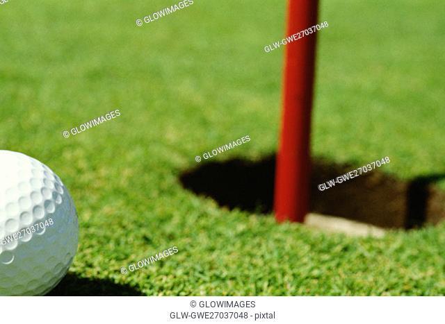Close-up of a golf ball near a hole