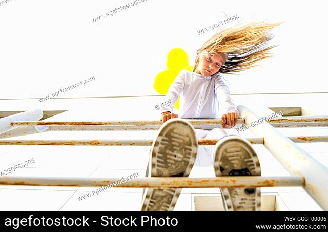 Low angle view of girl standing on railing with tousled hair during sunny day