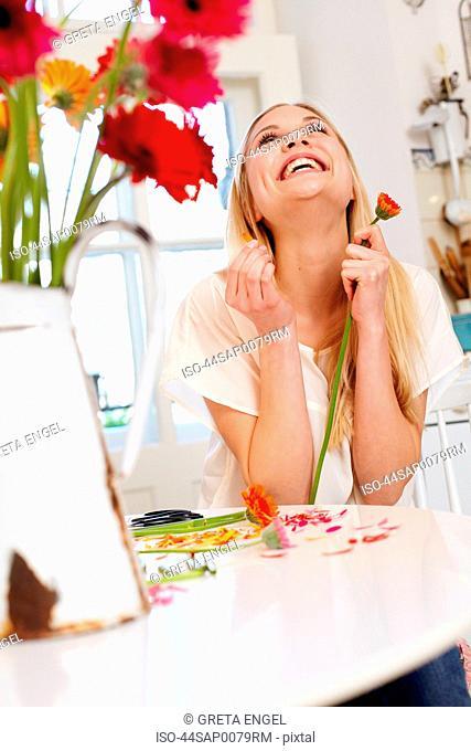 Woman picking petals off flower