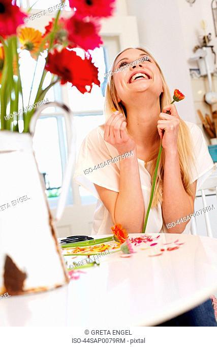 Woman picking petals off flower