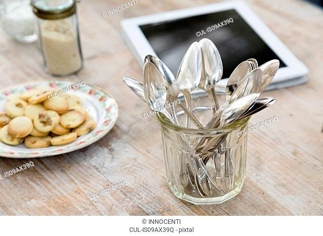 Digital tablet, plate of cookies and jar of spoons on wooden surface