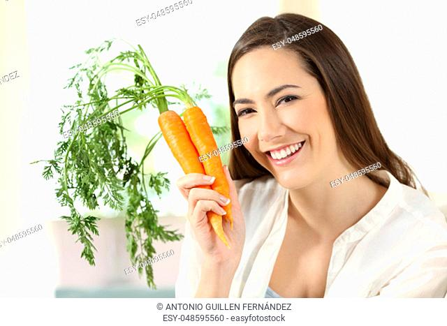 Portrait of a girl showing a bundle of carrots looking at camera sitting on a couch in the living room at home