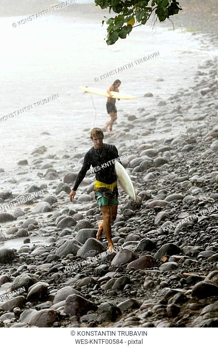 Indonesia, Bali, two surfers carrying surfboards in rain