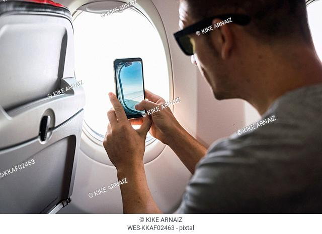 Man in airplane, using smartphone, taking a picture, airplane window