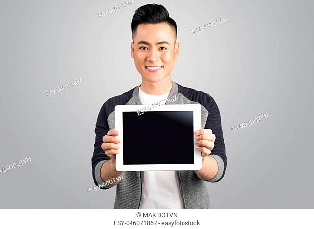 Confident young asian businessman showing digital tablet screen