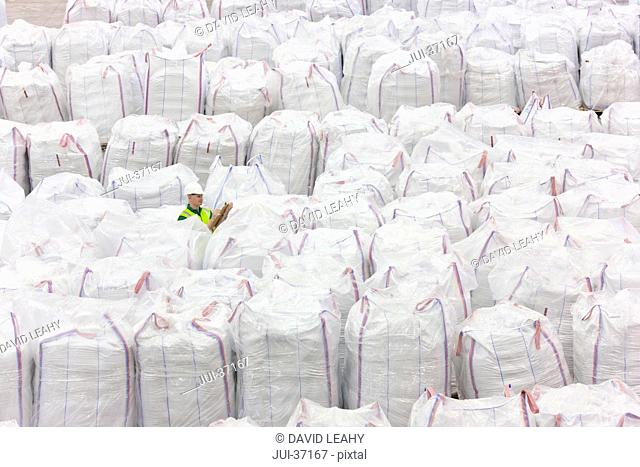 Worker among large bags of plastic pellets in warehouse