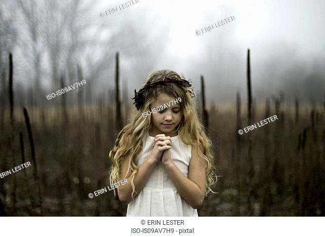 Portrait of long blond haired girl with head bowed in misty marsh