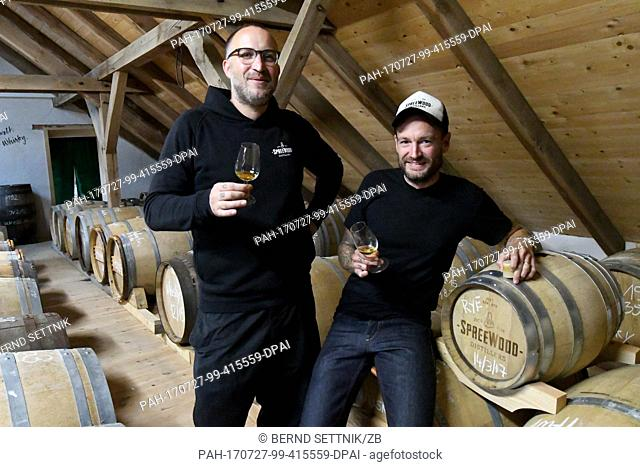 Owners Steffen Lohr (l) and Bastian Heuser test a whiskey in their storage in Schlepzig, Germany, 26 July 2017. Since October 2016