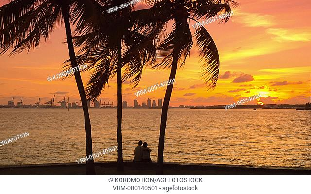 ZOOM OUT YOUNG COUPLE WATCH SUNRISE MIAMI BEACH SKYLINE FROM RICKENBACKER CAUSEWAY MIAMI FLORIDA USA