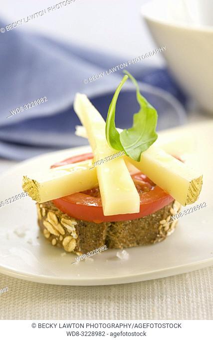 Montadito de queso manchego, rucula y tomate