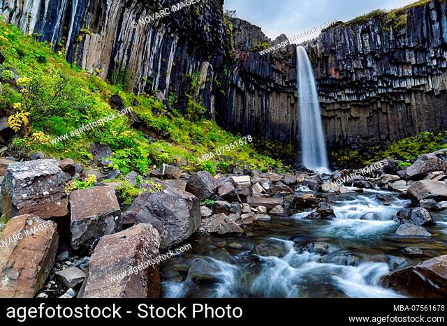 Svartifoss waterfall in autumn with watercourse in long term exposure, Skaftafell National Park, Iceland