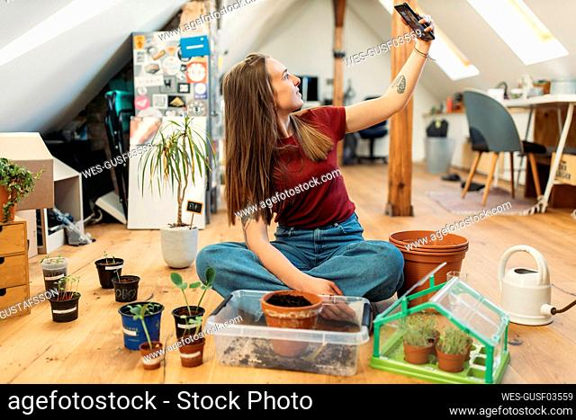 Young woman taking selfie with plants on wooden floor