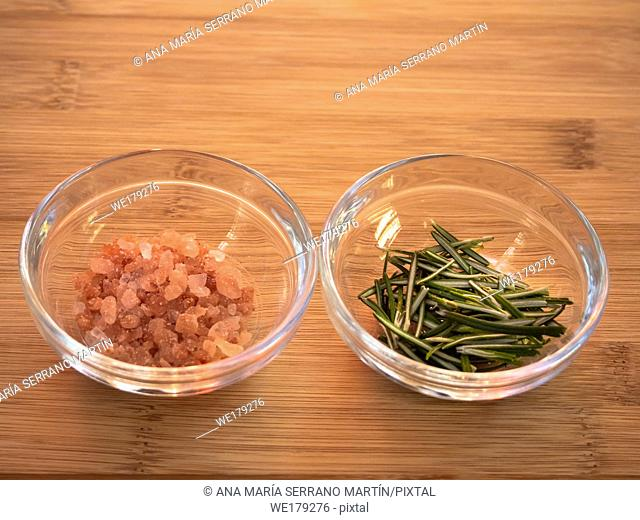 Crystal bowls with himalayan pink salt and rosemary on a wooden table