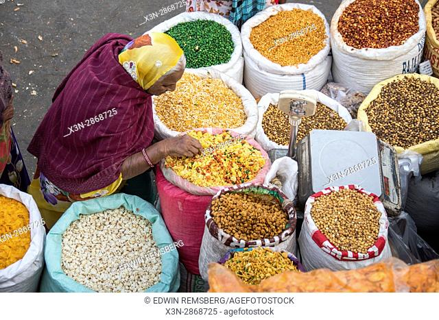 Indian woman sorting through grains being sold at an open market in Jaipur, India