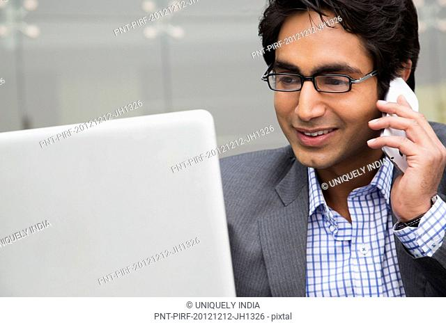 Businessman using a laptop while talking on a mobile phone