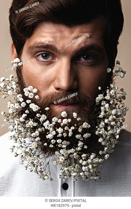 Creative Portrait of young beautiful man with a beard decorated with flowers
