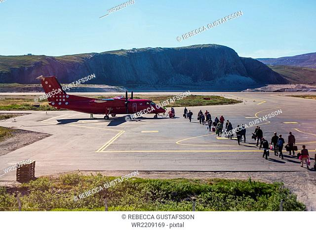 High angle view of people walking toward airplane parked at runway