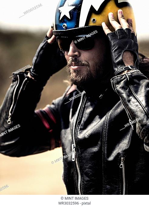 Bearded man wearing black leather jacket and sunglasses adjusting his yellow open face crash helmet