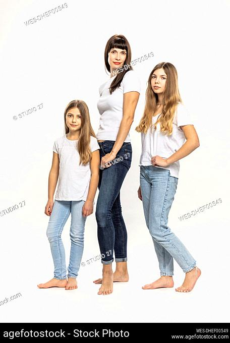Mother standing with daughters against white background