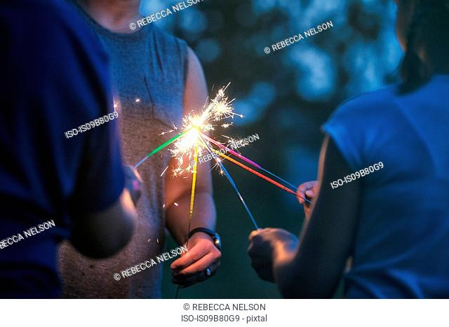 Cropped shot of women and girl igniting sparklers together at dusk on independence day, USA