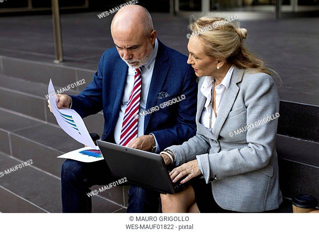 Senior businessman and businesswoman sitting on stairs with laptop and charts