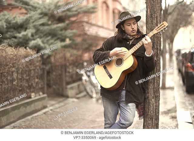 man playing guitar at street in city