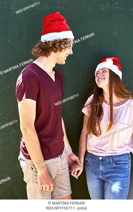 Young couple wearing Christmas hats smiling at each other