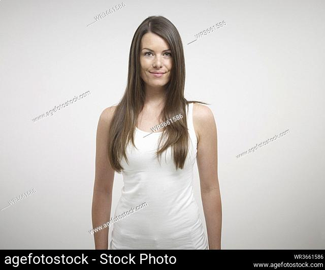 Portrait of young woman standing against white background, smiling