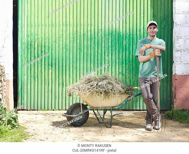 Man with wheelbarrow full of hay